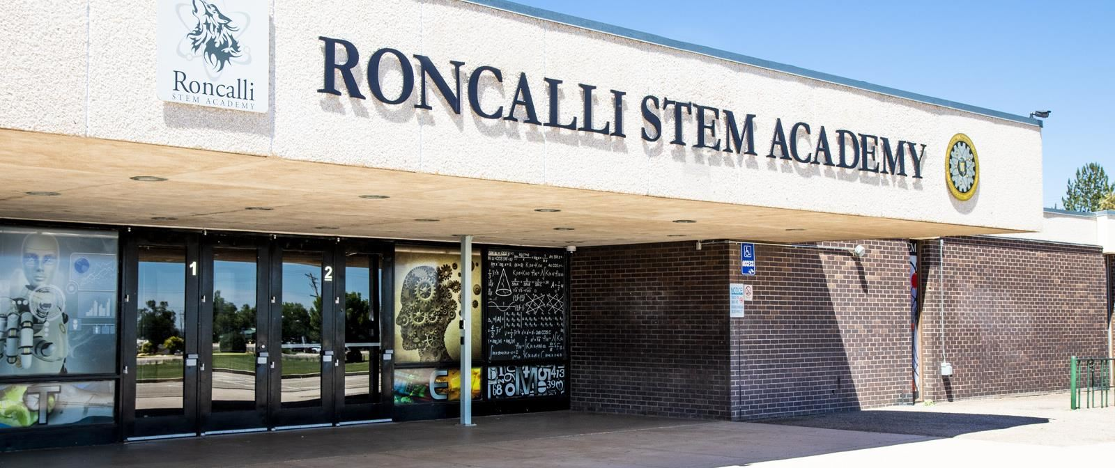 Front of Roncalli STEM Academy with glass doors on a sunny day