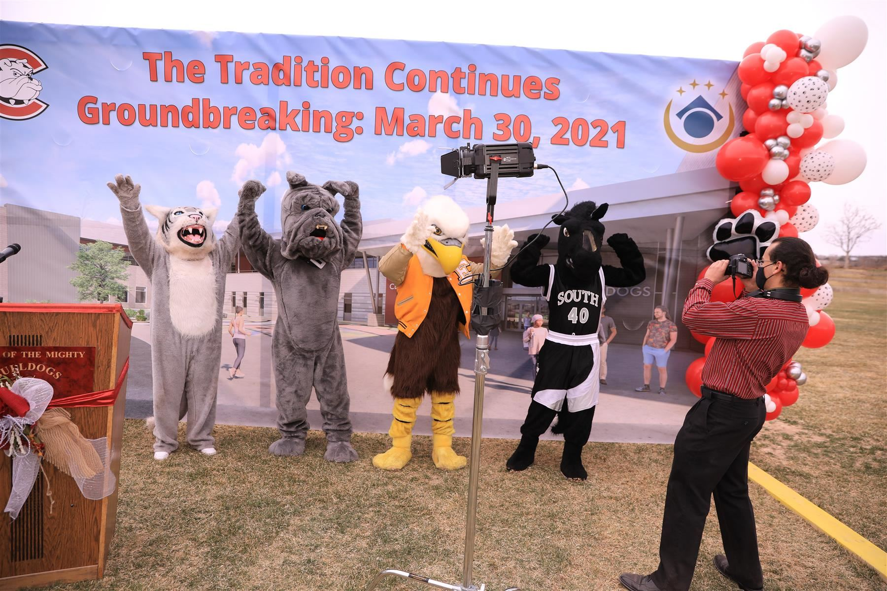A Centennial student takes a photo of all four mascots at the groundbreaking