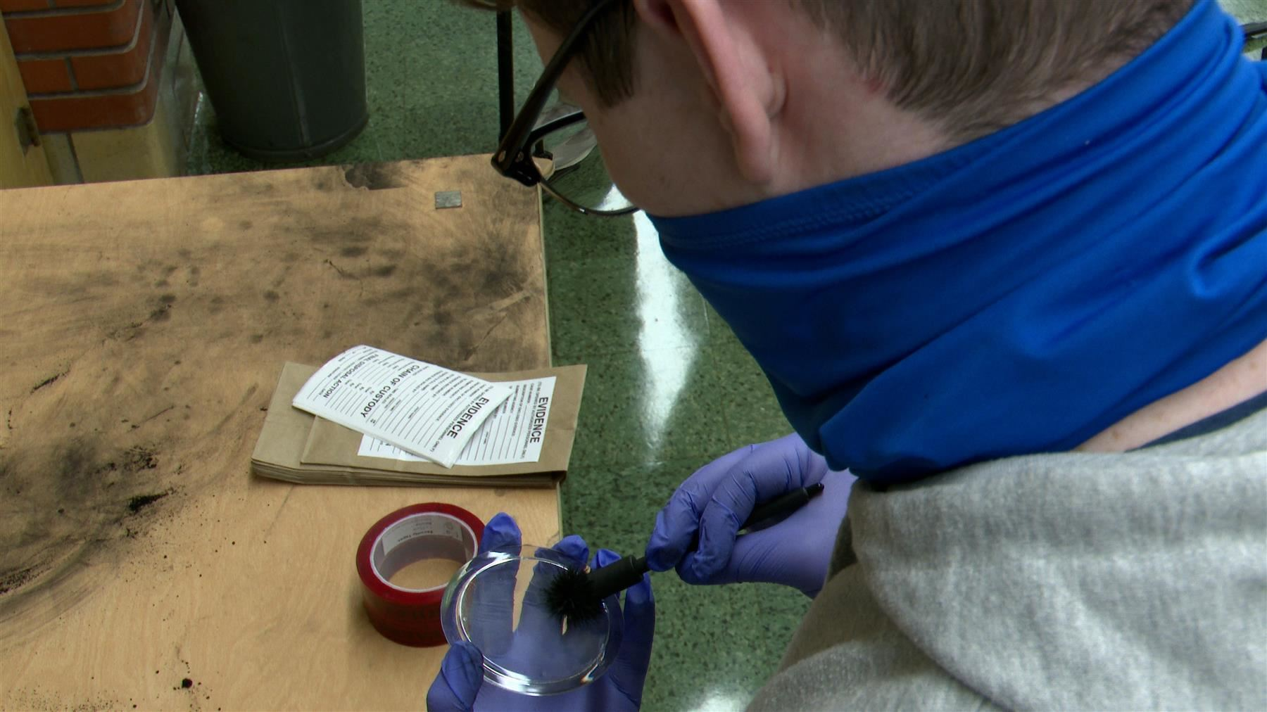 A south student uses tools to discover fingerprints as part of the Criminology course at his school