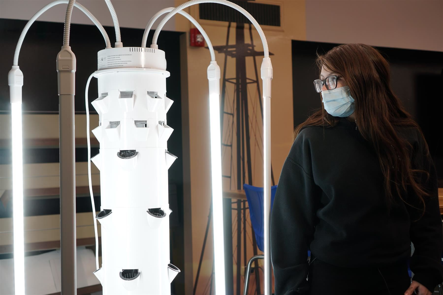 A student observes the new virtual grow tower at Roncalli