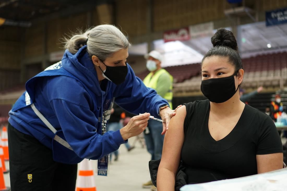 D60 Nurse, Jessica McDonald administers a vaccine to a patient
