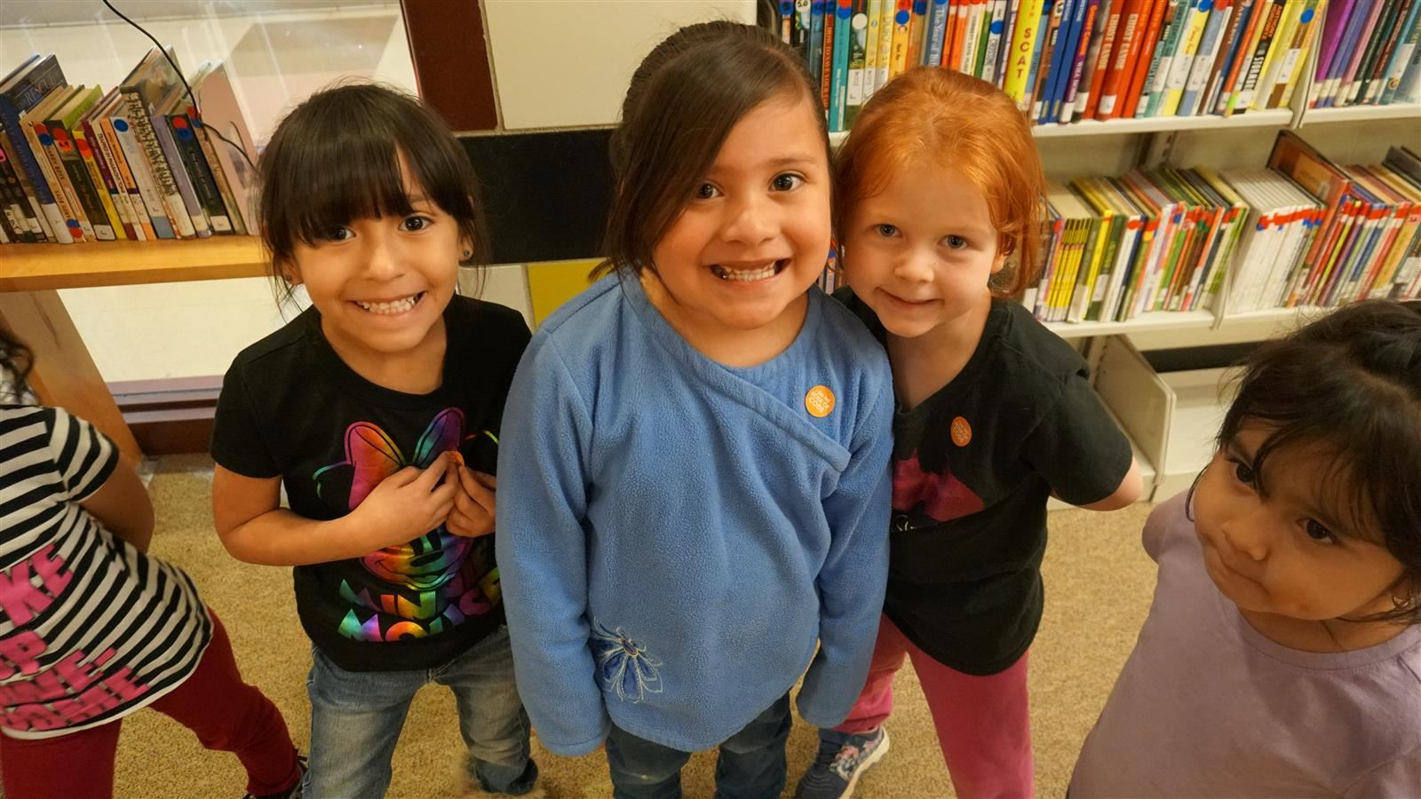 Three students smiling at the camera during the Hour of Code event at their school