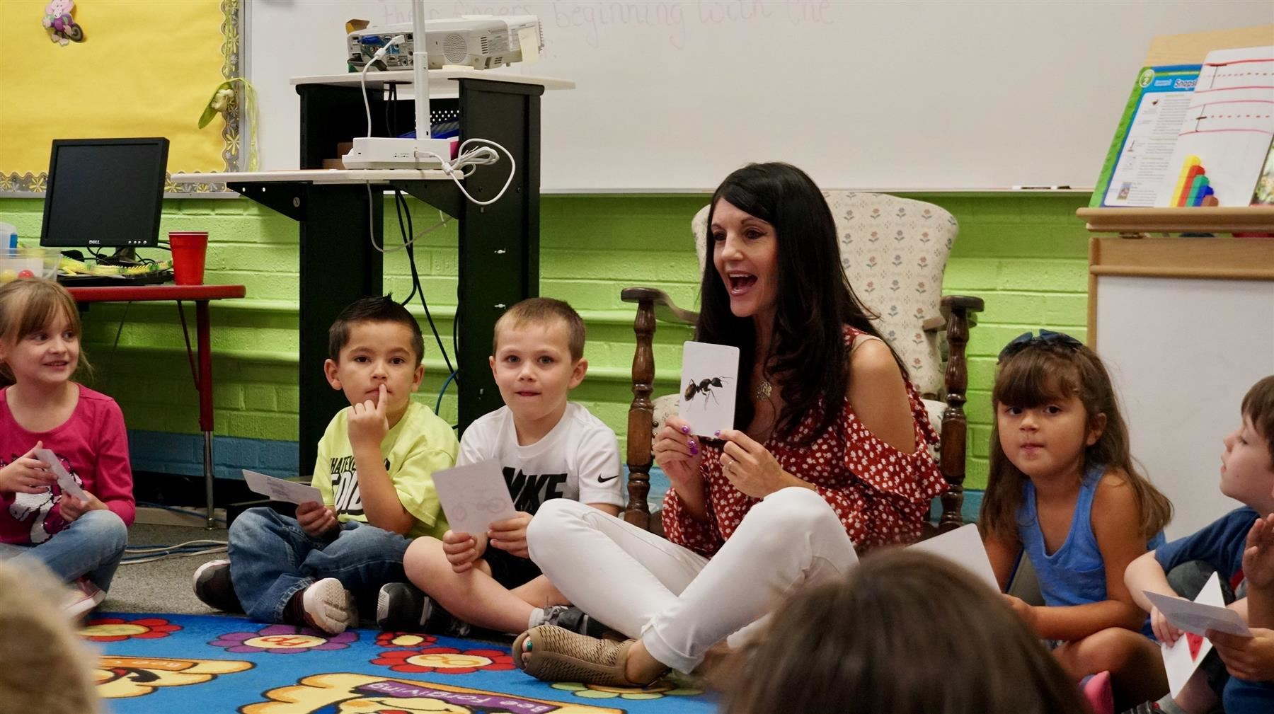 A kindergarten teacher shows with flashcards to her students