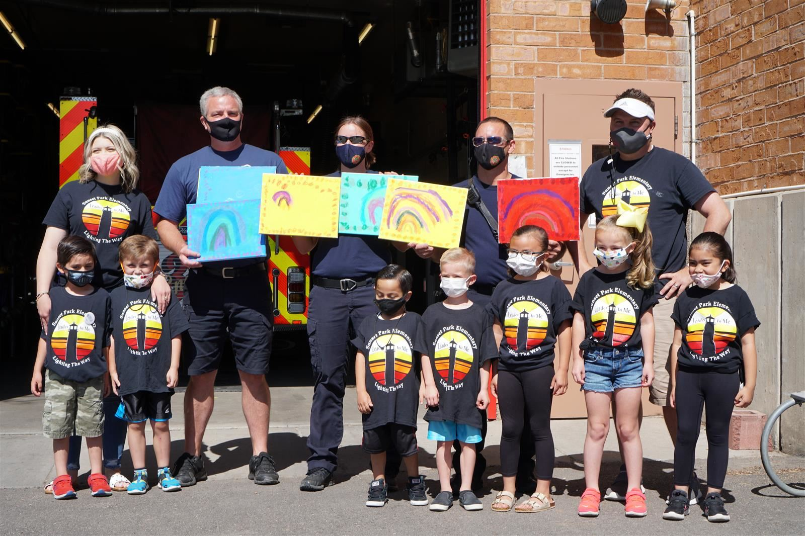 Sunset Park Kindergarteners and their teachers standing with firefighters from Fire Station 7