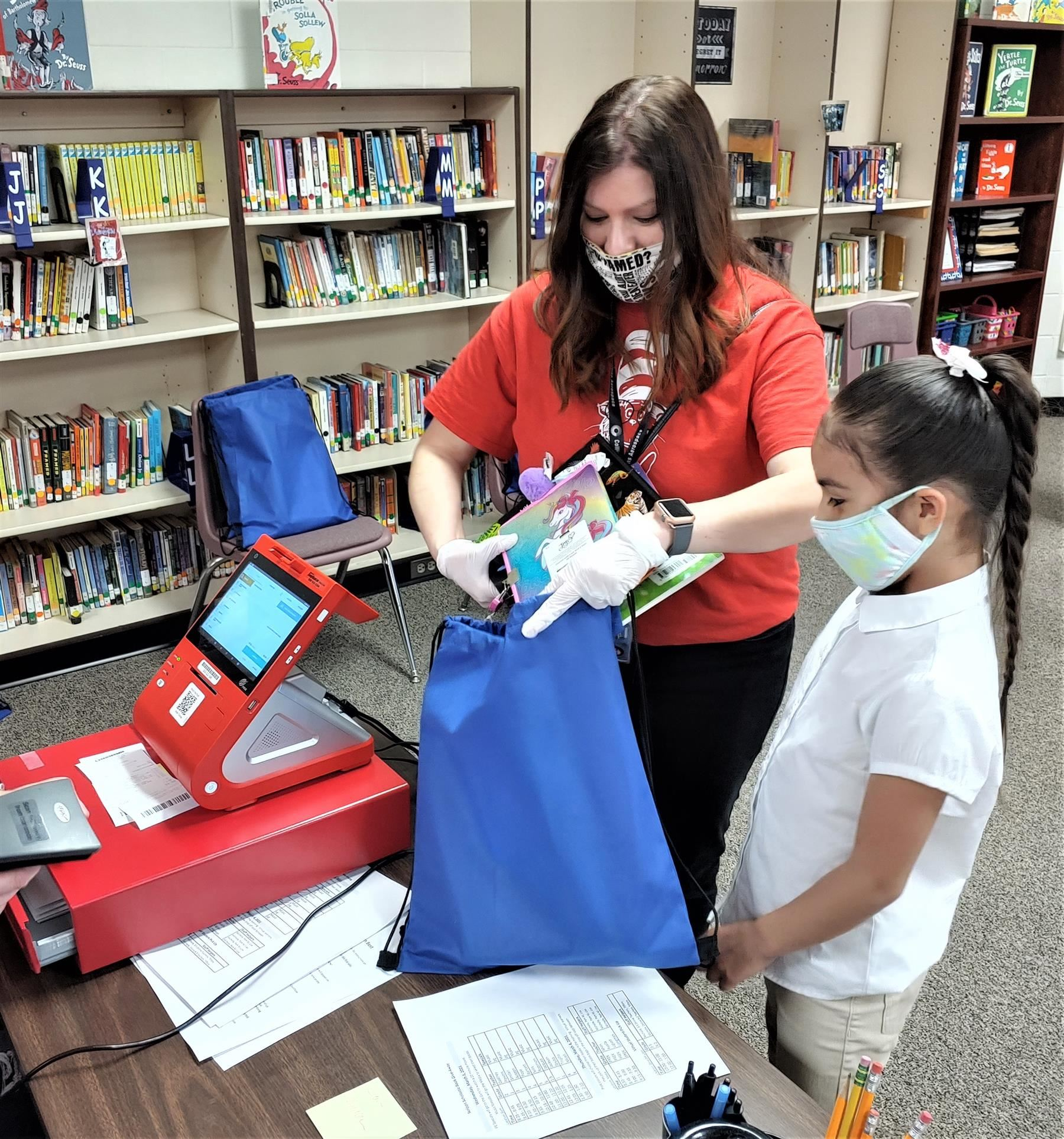 Michelle Padilla helps load a students bag with new books from the book fair
