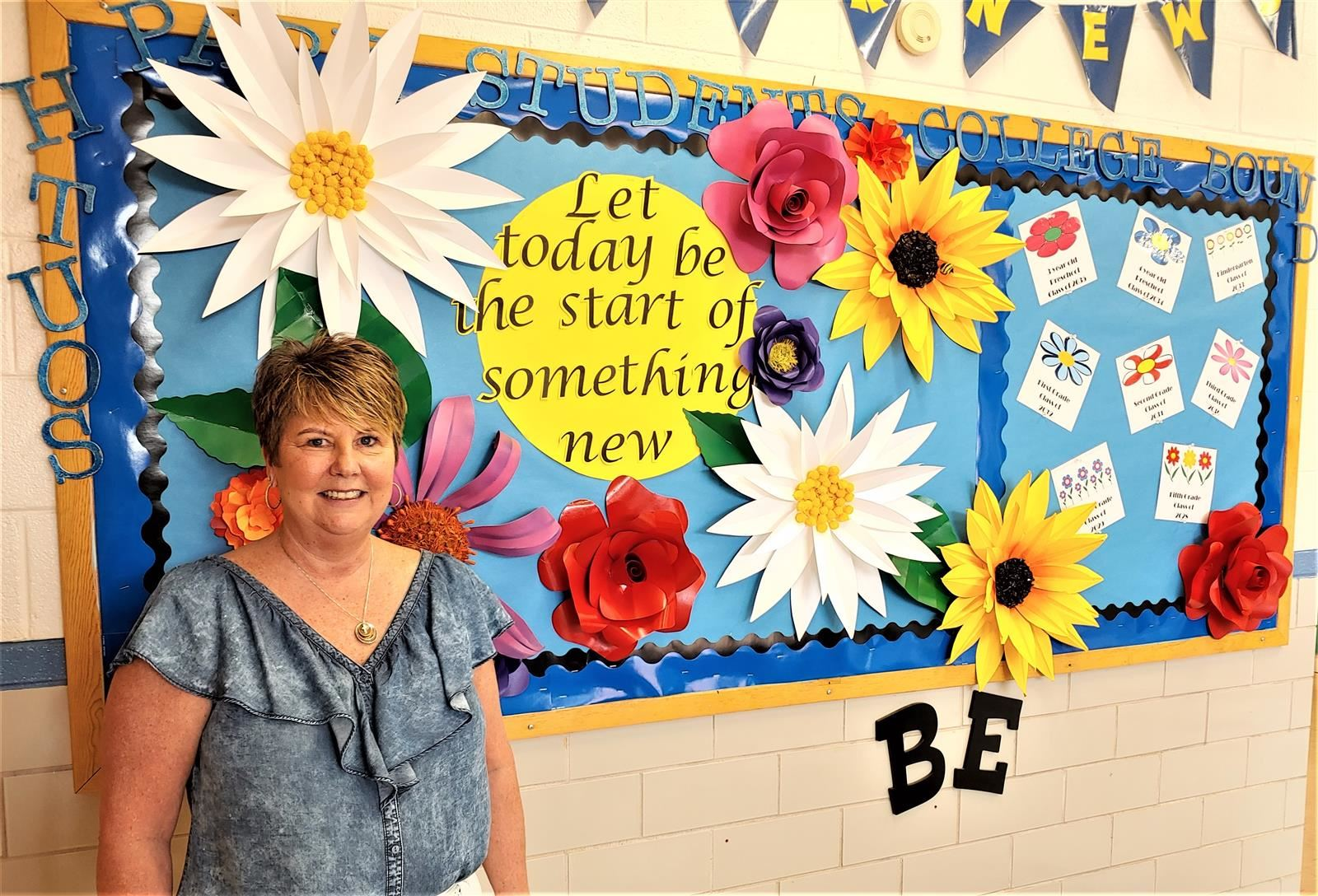 Principal Brunjack stands in front of a bulletin board decorated for spring